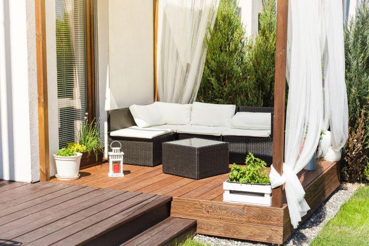 Terrassenecke mit Lounge, Sichtschutz durch weiße Vorhänge