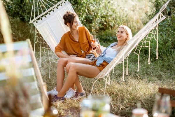 man erkennt zwei Frauen, die in der Hängematte auf der Terrasse entspannen