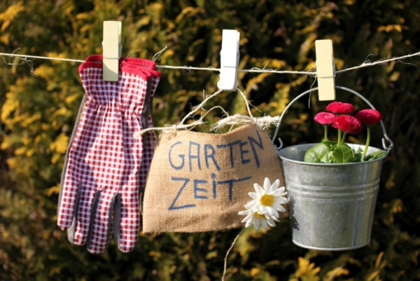 """Zu sehen sind Kübelpflanzen, Handschuh und ein Täschchen mit der Aufschrift """"Gartenzeit""""."""