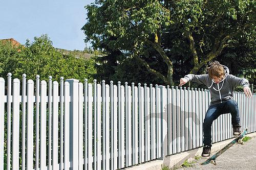 Kombinierter Latten- und Palisadenzaun in weiß mit Rundkappen, Modell Milano von GUARDI, Kind macht Skateboard Trick vor Zaun