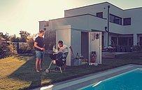 Gartenhaus aus Stahl in silber metallic steht neben einem Pool, davor grillen zwei Freunde