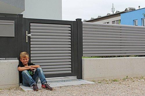 Gehtür aus Lamellen in grau mit Rahmenoptik in anthrazit, Modell Plissée, mit passendem Briefkasten, Kind sitzt vor Zaun am Boden