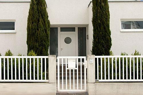 Schlichter Einzelstabzaun in weiß mit passender Gartentüre und integriertem Briefkasten, Modell Siena, vor einem weißen, modernen Haus