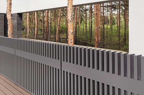 Moderner Gartenzaun aus Aluminium mit senkrechten Stäben in grau markiert einen Hauseingang