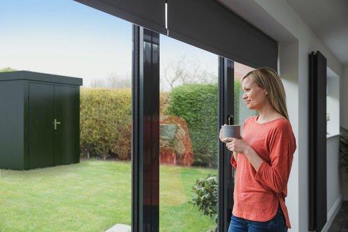 Gartenhaus in Größe L in anthrazit mit Doppelflügeltor stehr draußen im Garten, im Inneren des Hauses steht eine Frau mit Kaffeetasse in der Hand und sieht verträumt ins Freie