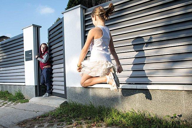 Zwei Kinder spielen vor einem Sichtschutzzaun aus Aluminium mit passendem geöffnetem Gartentor in grau
