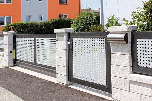 Gartentüre mit Lochblechfüllung in weiß mit schwarzer Rahmenoptik, Postkasten in Steinsäule integriert, Modell Loos von GUARDI