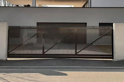 Schiebetor aus Aluminium mit senkrechten Latten und Schrägkappen in anthrazit