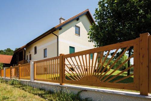 Schlichter Einzelstabzaun in Holzoptik mit aufgehende Sonne Element, Modell Siena von GUARDI, vor gelbem Haus im Landhausstil