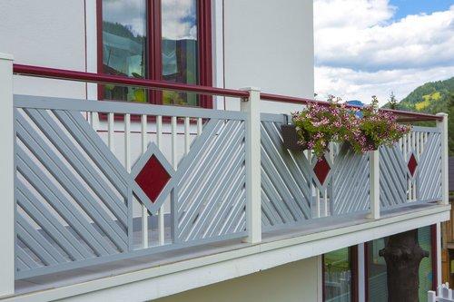 Balkongeländer aus Aluminium in grau mit rotem runden Handlauf, dahinter sieht man rote Fensterrahmen und weiße Hausfassade