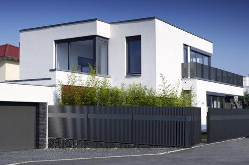 Lattenzaun in anthrazit mit passender Gartentüre designed von Studio F.A. Porsche, Modell Epos, vor modernen, weißem Haus