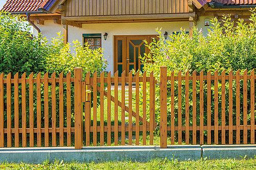 Gartentüre aus Latten in Holzoptik, Modell Treviso von GUARDI, vor Haus mit Garten