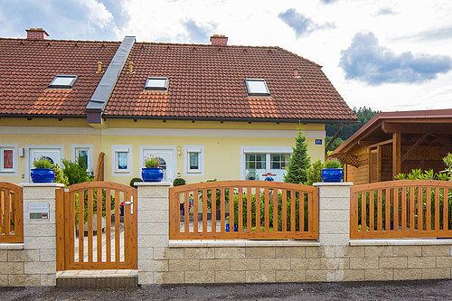 Füllungszaun in Holzoptik mit passender Gartentüre in Holzoptik, Modell Umbria konvex rund, in Steinmauer integriert vor gelbem Haus