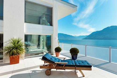 Balkon mit Lochblechfüllung in weiß, mit Handlauf Comfort, Modell Loos, Balkon mit Liege und Pflanzen, Ausblick auf See und Berge