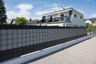 Doppelstabmatten mit Sichtschutzstreifen eingefädelt umzäunen ein Grundstück