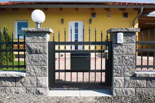 Gartentüre konvex in anthrazit mit Dekorringen und Lanze, mit passendem Briefkasten, Modell Venezia, vor gelbem Haus in Steinmauer integriert