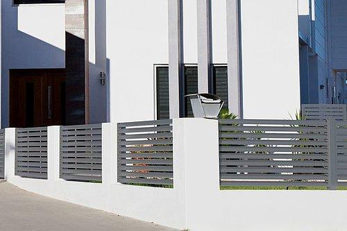 Lamellenzaun in grau, Modell Plissée, vor einem weißen, modernen Haus