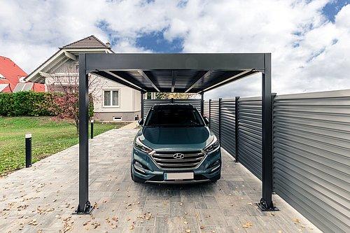 Carport Modell Pantheon in anthrazit schützt ein Auto in der Einfahrt
