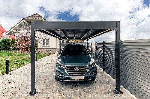 Carport Modell Pantheon in anthrazit, im Carport steht ein SUV in ähnlicher Farbe