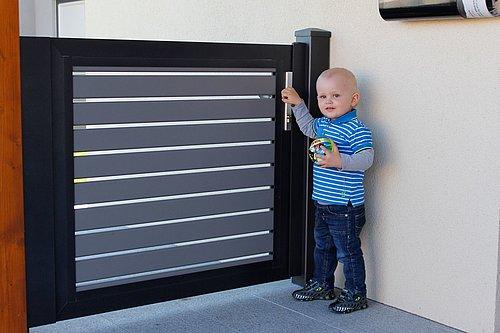 Gartentüre aus Latten in grau mit schwarzer Rahmenoptik, Modell Nouveau, Kleinkind öffnet die Gehtüre
