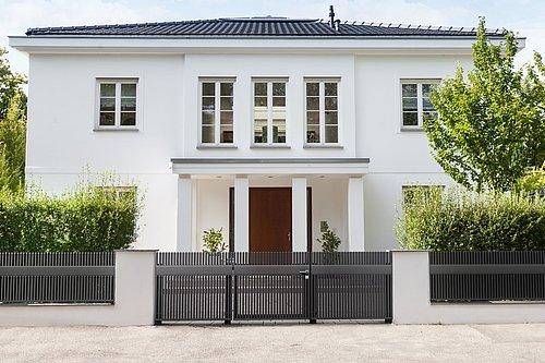 Lattenzaun in anthrazit mit Doppelflügeltor vor weißer Villa