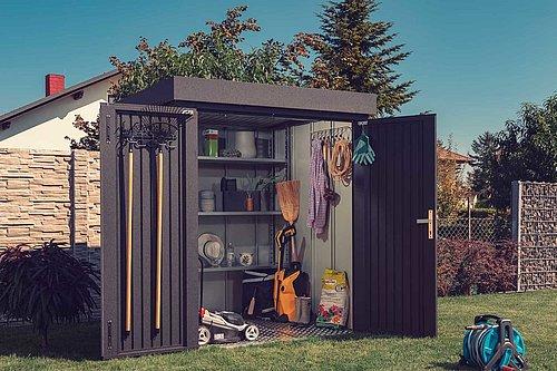 moderne Gartenhütte aus Stahl in anthrazit steht geöffnet im Garten, darin sind diverse Werkzeuge zu sehen