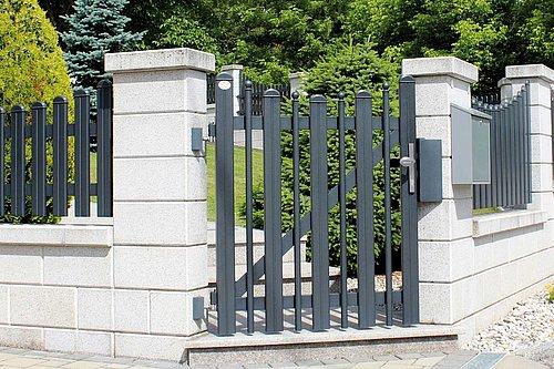 Gartentüre mit Kugeln in Grau, Modell Milano konkav rund, in Steinmauer integriert vor Garten mit Bäumen