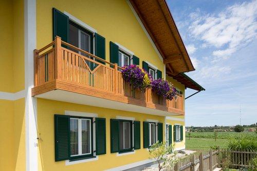 Balkongeländer in Holzoptik im Modell Kitzbühel, der Balkon ist auf einem gelben Haus montiert, die Fenster haben grüne Rahmen