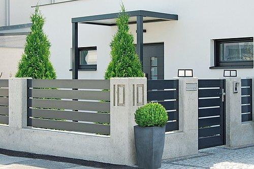 Lattenzaun in anthrazit mit passender Gartentür, Modell Triest von GUARDI, vor einem modernen, vor einem modernen, weißen Haus
