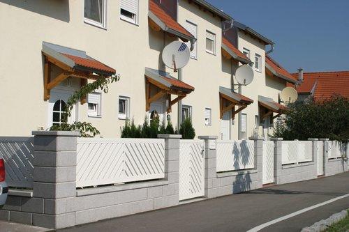 Schützender Füllungszaun aus Aluminium in weiß, Modell Umbria doppelt-diagonal A-Form von GUARDI, in Steinmauer integriert vor gelbem Reihenhaus
