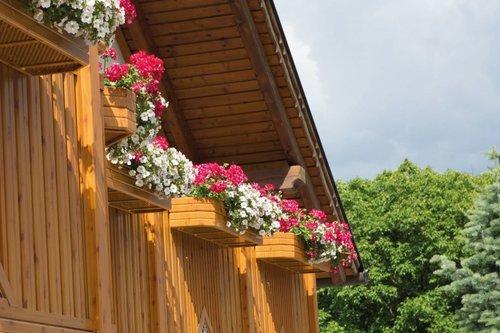 Blumenkist aus Aluminium in Holzoptik, vier Stück sind nebeneinander montiert mit blühenden Blumen darin