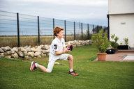Ein Junge spielt mit einem Football vor einer Doppelstabmatte in anthrazit