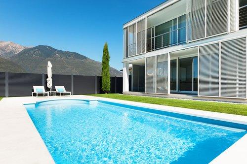 Lattenzaun in anthrazit, Modell Nouveau von GUARDI, im Vordergrund ein modernes Haus mit Pool