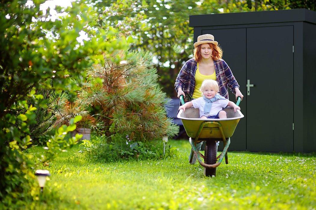 Gartenhaus aus Stahl in anthrazit steht im Garten, davor eine junge Frau mit einem Kind in der Scheibtruhe