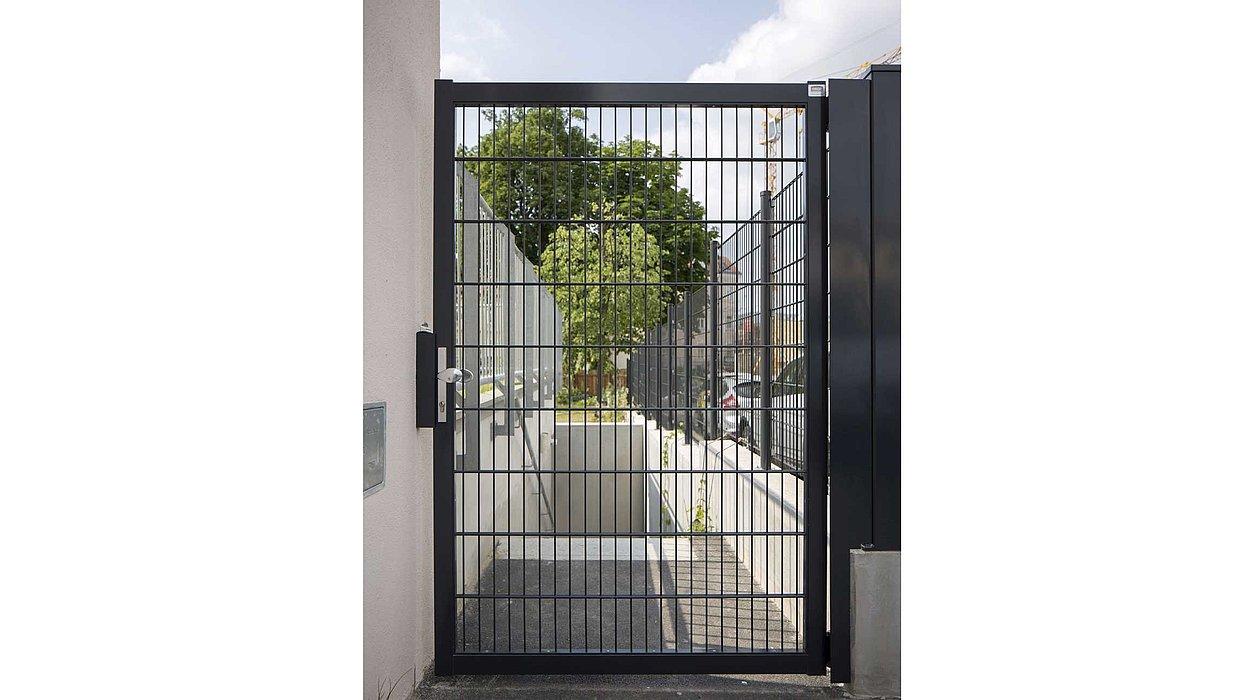 Doppelstabmatten-Tor in anthrazit begrenzt einen Eingangsweg