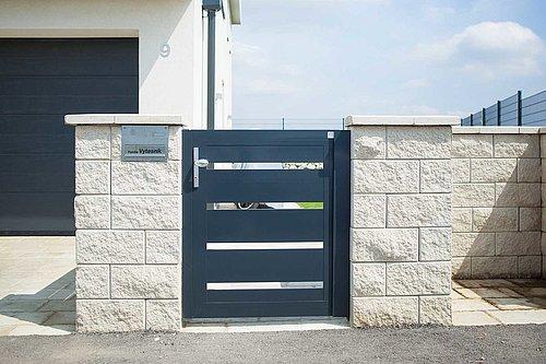 Moderne Gehtüre aus Aluminium in anthrazit, Modell Triest, integriert in Steinmauer, Garage im Hintergrund