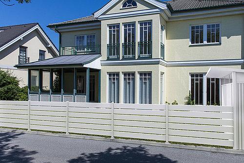 DIY Stecksystem Zaun in weiß mit weißen Stehern, Modell Stecksystem, vor gelblicher Villa, do it yourself Zaun