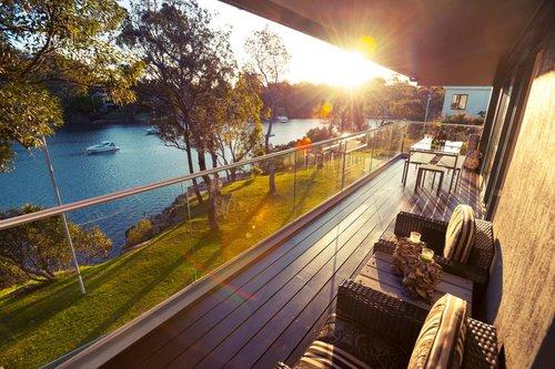 Glasbalkon von Guardi mit rundem Handlauf, davor Balkonmöbel, dahinter sieht man einen Fluss mit Sonnenuntergang