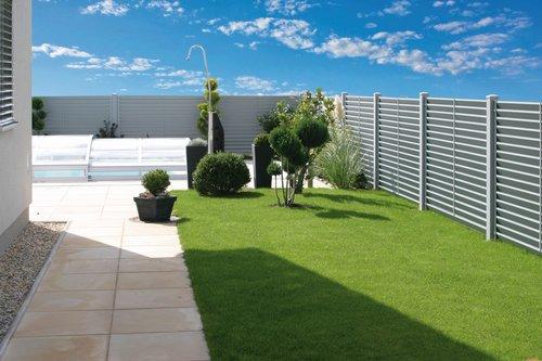 Blickdichter Lamellenzaun in metallic, Modell Trento von GUARDI, steht in einem Garten mit Pool