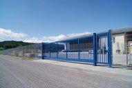 Blaues Schiebetor aus Aluminium sichert ein Firmengelände ab