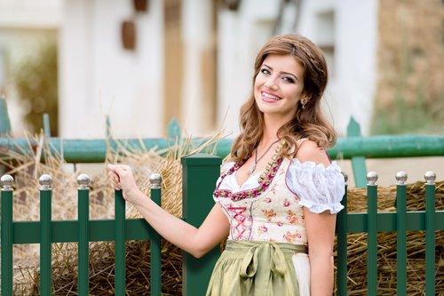 Palisadenzaun in grün mit silbernen Kugeln, Modell Gloriette standard von GUARDI, Frau im Dirndl steht vor Zaun