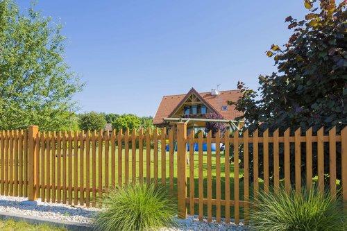 Alu-Jägerzaun in Holzoptik, Modell Treviso, vor Haus mit großem Garten mit Aufstellpool und Schaukel