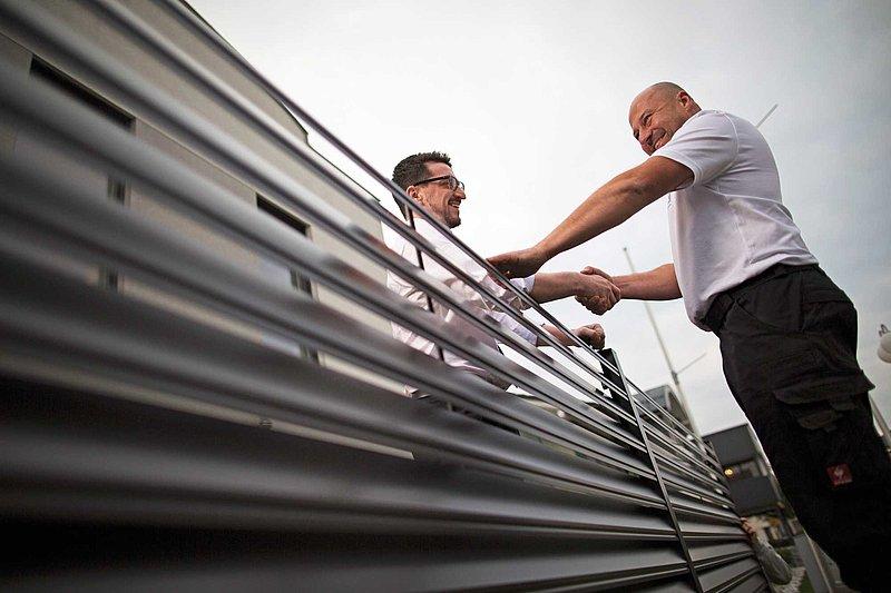 GUARDI Mitarbeiter reicht einem Kunden über einen Gartenzaun aus Aluminium die Hand